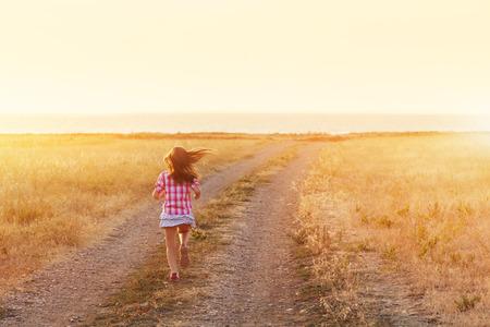 Meisje dat op de weg bij zonsondergang