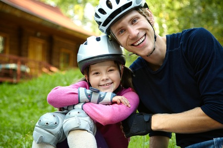 portrait of a sports dad and daughter in a helmet. Dad with his little daughter on the skates photo