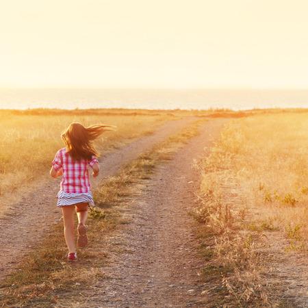 Little girl running down the road at sunset Standard-Bild