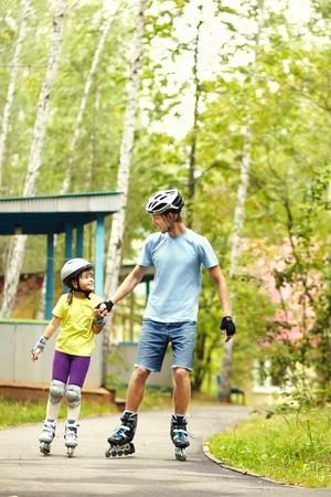 Vader en dochter rolschaatsen.
