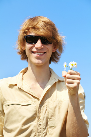 giver: Portrait of a young man in sunglasses with flower