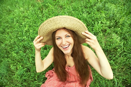 beautiful smiling dreaming woman in a hat lying on the grass photo