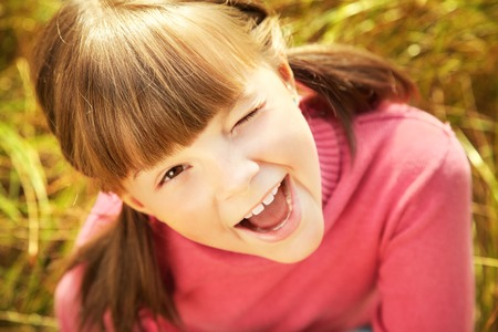 Portrait of a cheerful happy cute winking girl closeup photo