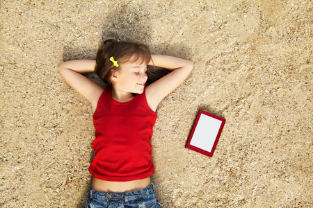 little girl lying on the sand with a tablet computer  photo