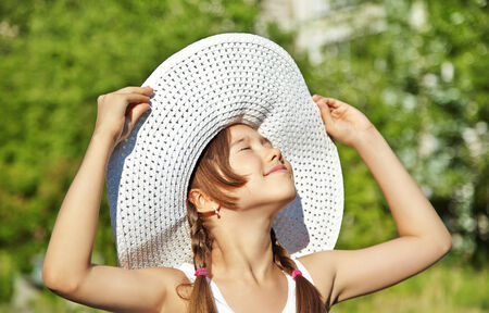 portrait of a cute teenage girl in wide-brimmed hat on a background of green in summer park photo