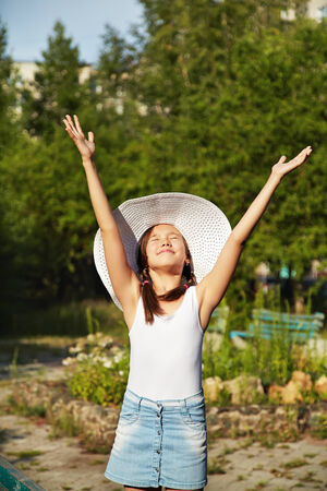 cute joyful teenage girl in wide-brimmed hat with arms raised on a background of green in summer park photo
