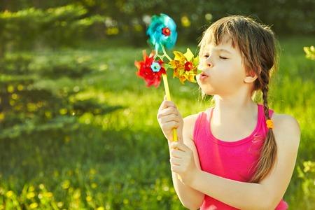녹색 배경에 공원에서 바람개비와 함께 연주 명랑 소녀 스톡 콘텐츠