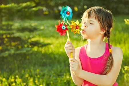 cheerful little girl playing with pinwheel in the park on a green background
