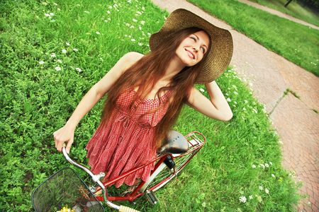 young woman in a hat with a bike sitting in the park near the tree . Active people. Outdoors photo