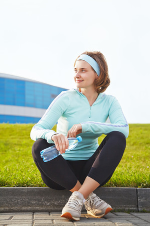 Portrait of sporty smiling woman with a water bottle on a grass background. outdoor sports photo
