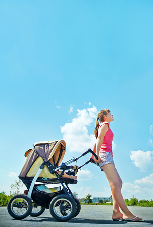 young mother on a walk in the park with a baby in a stroller photo