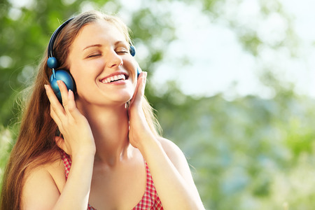 Beautiful Relaxing Young Woman with Headphones Outdoors photo
