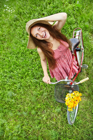 young woman in a hat with a bike in the park. Active people. Outdoors photo