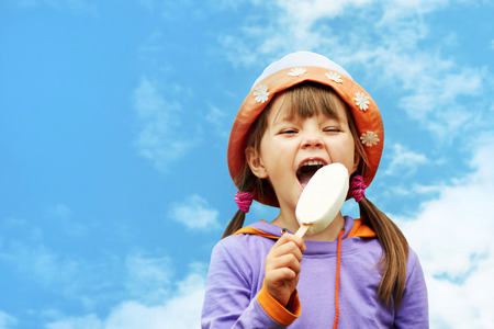little girl in hat eating ice cream on a background of sky