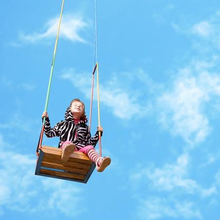 happy little girl on a swing on sky background Standard-Bild
