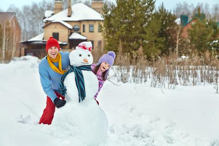 bonhomme de neige: dr�le de papa et la fille avec un bonhomme de neige. Famille marcher � l'ext�rieur en hiver Banque d'images