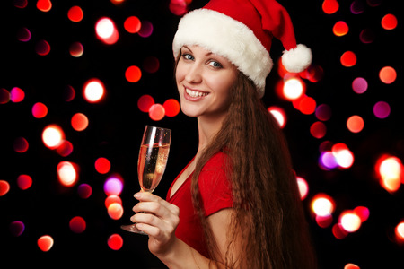 attractive woman in santa hat with a glass of champagne on a background of blurred lights. Christmas party