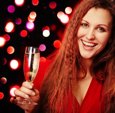aantrekkelijke vrouw met een glas champagne op een achtergrond van wazig lights. Kerstfeest Stockfoto
