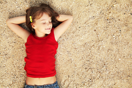 laying on back: smiling cute little girl lying on the sand. child on vacation