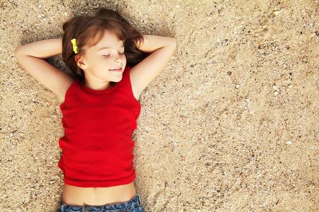 mignonne petite fille: sourire mignonne petite fille couch�e sur le sable. enfant en vacances Banque d'images