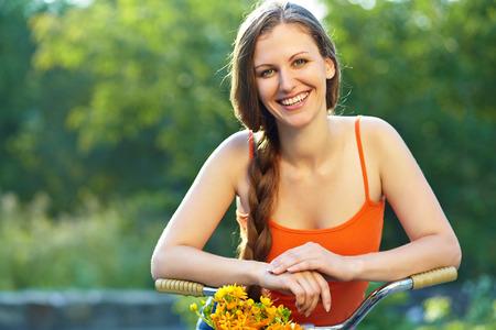jonge vrouw met een fiets in een zomer park. Actieve mensen. Buitenshuis Stockfoto