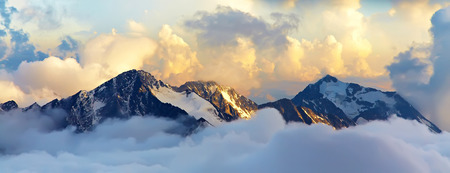 summer landscape: alpine landscape with peaks covered by snow and clouds. banner. panorama