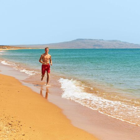 purposeful: Man running in water on the beach. jogging along the coastline. outdoor sports