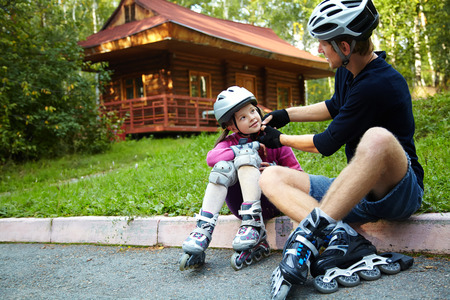 skate: portrait of a sports dad and daughter in a helmet. Dad with his little daughter on the skates Stock Photo