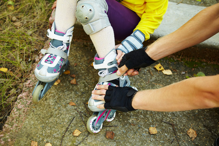 Dad helps his daughter to dress roller skates photo