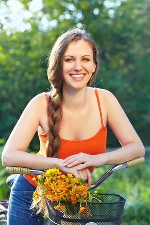 young woman with a bike in a summer park. Active people. Outdoors Standard-Bild