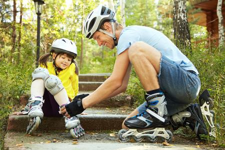 portret van een sportieve vader en dochter in een helm. Papa met zijn dochtertje op de schaatsen Stockfoto