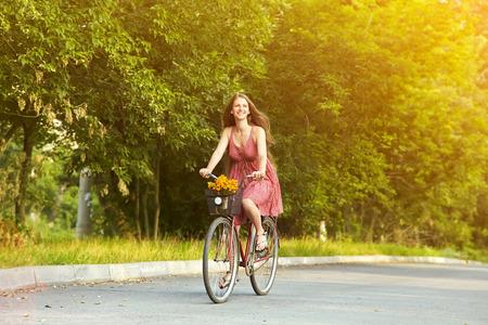 mooie jonge vrouw rijdt op een fiets in een park. Actieve mensen. Buitenshuis Stockfoto