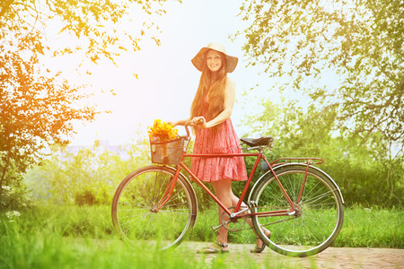 young woman in a hat with a bike in the park. Active people. Outdoors