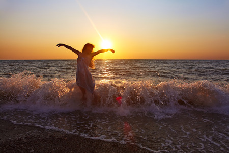 Mooie romantische vrouw bij de kust bij zonsondergang