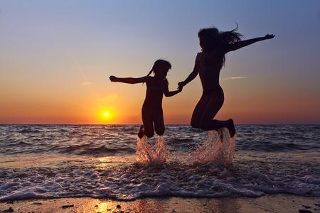 어머니와 딸 해변에서 재미. 해변에서 휴가를 보내다.