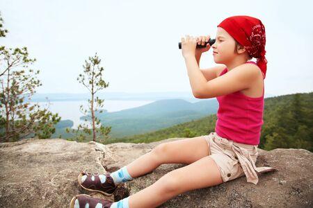 bandana girl: funny little girl in a bandana with a spyglass. children outdoors Stock Photo