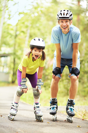 roller skate: portrait of a sports dad and daughter in a helmet. Dad with his little daughter on the skates. two people