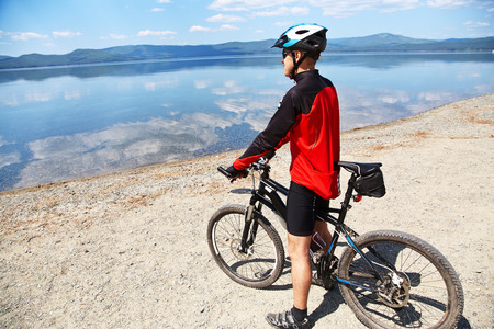 admires: cyclist admires the scenic views of the mountain lake. man outdoors