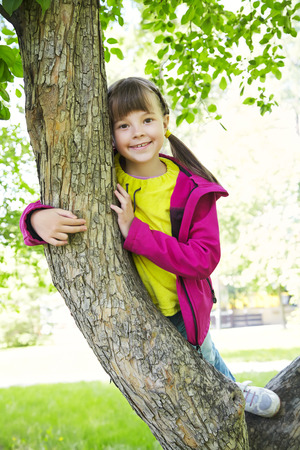 naivety: Funny playful little girl sitting on a tree in the park. children outdoors. vacation in the summer park