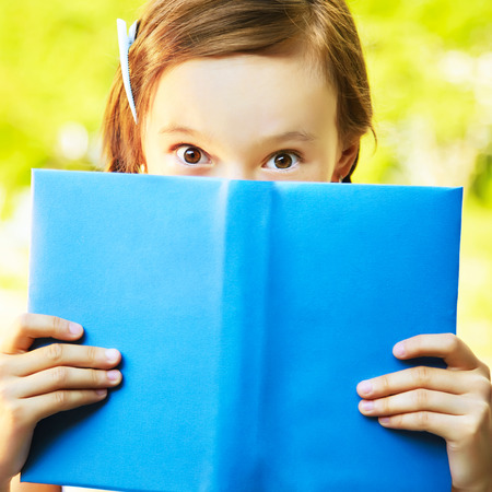 girl looks out from behind a blue book. reading, learning and education