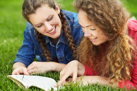 Two friends reading a book lying on the grass in the summer park .  youth lifestyle