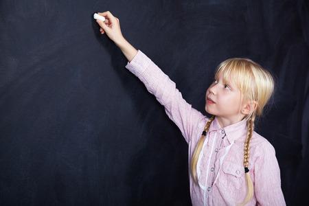 schoolchild: schoolchild writes with chalk on a blackboard. School and education