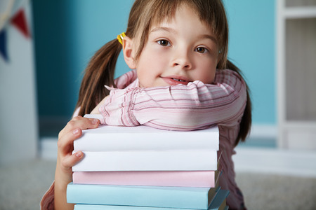 children learning: girl with a stack of books. School and education