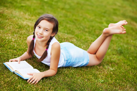 meisje liggend op het gras in het park en het lezen van een boek. lezen, leren en onderwijs