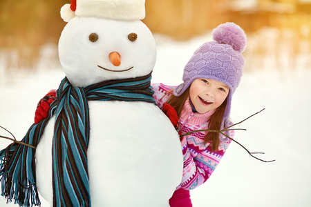 snowmen: happy kid playing with snowman. funny little girl on a walk in the winter outdoors