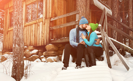hugging couple: man and woman sitting on the porch of a house. young happy couple in love outdoors in the winter Stock Photo