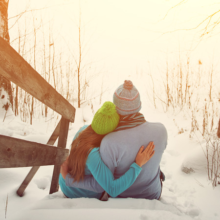 romantic hug: man and woman sitting on the porch of a house. young happy couple in love outdoors in the winter Stock Photo