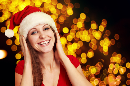 attractive woman in santa hat on a background of blurred lights. Christmas party