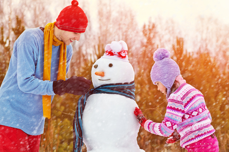 frosty the snowman: funny dad and daughter with a snowman. Family walking outdoors in winter Stock Photo