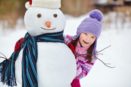 glückliches Kind spielt mit Schneemann. lustige kleine Mädchen auf einem Spaziergang im Winter im Freien Standard-Bild